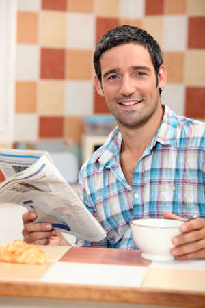 informed: Man reading the newspaper while having breakfast