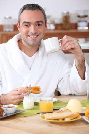 Man having breakfast in dressing gown photo