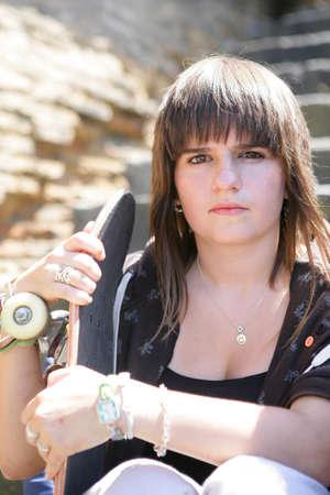 A teenage girl holding a skateboard photo