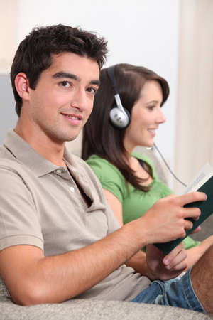 Man reading while his girlfriend listens to music photo