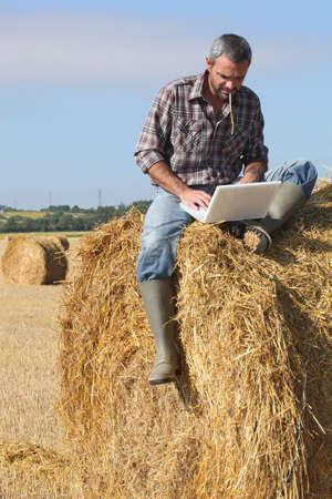 granjero: Agricultor con un ordenador port�til en un pajar