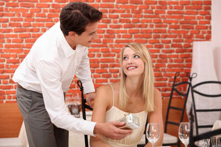 Man giving surprise gift to woman in restaurant photo