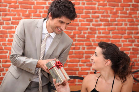 Man offering woman gift in restaurant photo