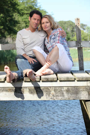 men 45 years: Barefoot couple by the water Stock Photo