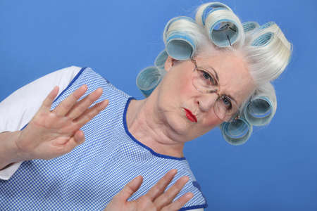 lamentation: grandmother with hair curlers against blue background
