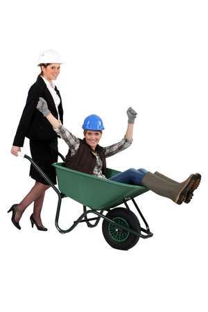 business tool: businesswoman carrying a craftswoman in a wheelbarrow Stock Photo