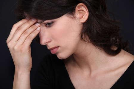 overwhelmed: A cute brunette having a headache.