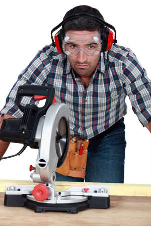 Man with goggles using band-saw photo