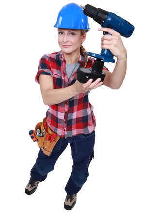power operated: Tradeswoman holding a battery-powered power tool