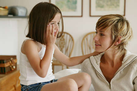 Little girl whispering secrets to her mom photo