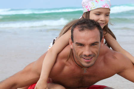 a little girl and her father playing on the beach photo