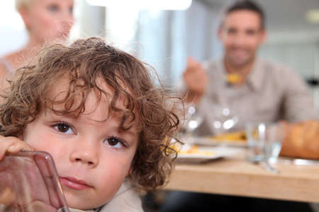 little boy sitting at table with parents in background Stock Photo - 12249025