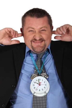 Man blocking his ears because of alarm clock photo