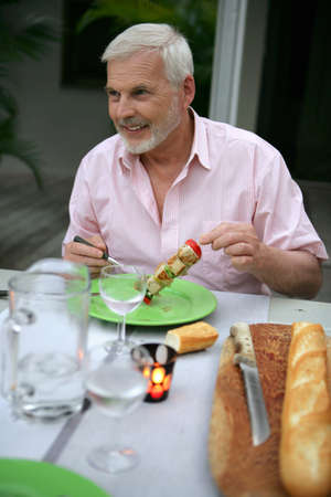 60s adult: senior man on vacation eating in a restaurant