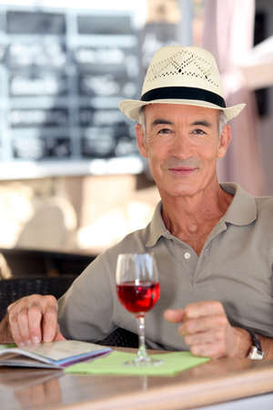 Older gentleman tourist drinking a glass of rose in a restaurant photo