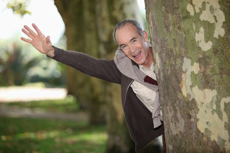 plaza of arms: Man jumping out from behind tree Stock Photo