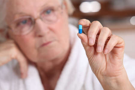 An old woman taking a pill. photo