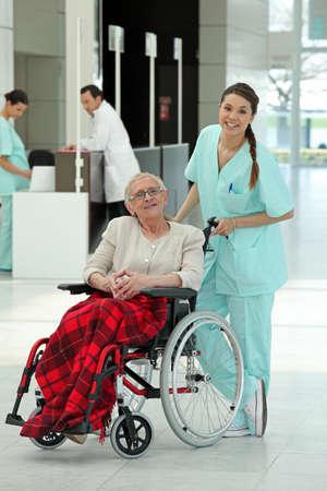 persona en silla de ruedas: Enfermera empujando a una mujer mayor en silla de ruedas Foto de archivo
