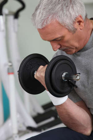 mature white-haired man lifting weight in sports room photo