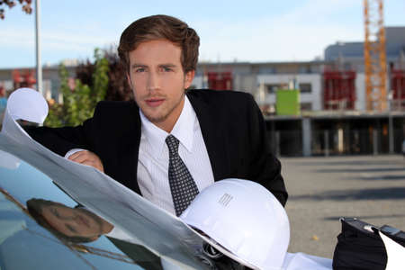 An engineer looking at a blueprint before a meeting photo