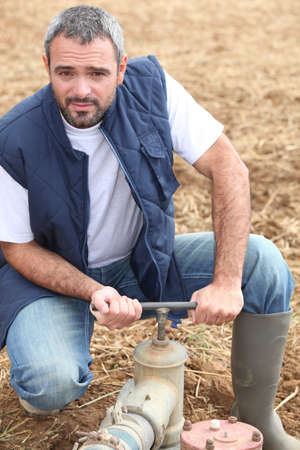 Farmer opening a water pipe photo