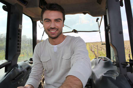 producers: Smiling man driving tractor