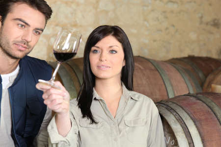 Couple in a cellar tasting wine photo