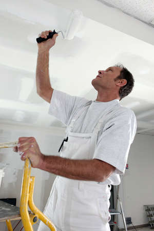 Man painting a ceiling white photo