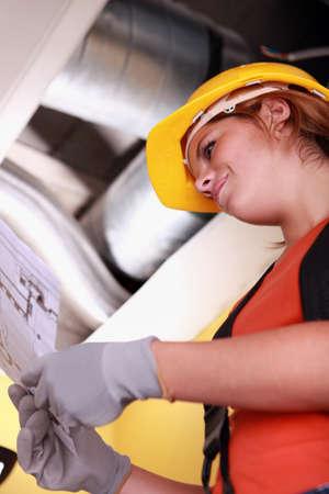 Tradeswoman reading a blueprint Stock Photo - 12251021