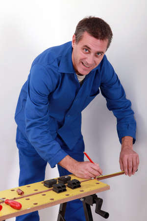 Happy plumber measuring copper pipe Stock Photo - 12251285