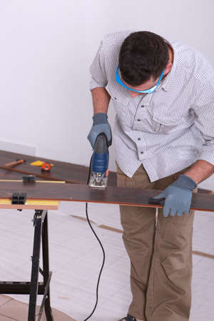 tongue and groove: Man using an electric jigsaw to cut a piece of wooden flooring Stock Photo