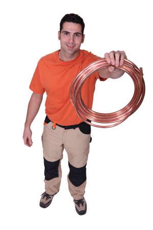Laborer holding copper pipe Stock Photo - 12250608