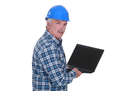 senior craftsman holding a laptop photo