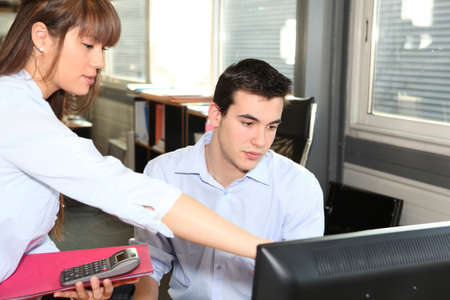 Woman explaining something on a computer to her colleague