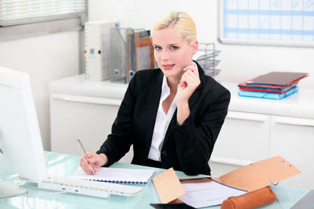 Blonde woman working at her desk Stock Photo - 12251022