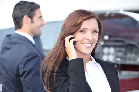 communicative: businesswoman on the phone and businessman in the background Stock Photo