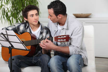 father and teenage son playing the guitar photo