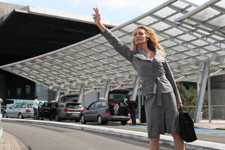 business airport: Businesswoman waving taxi