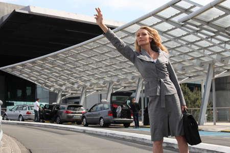 gente aeropuerto: Empresaria saludando taxis Foto de archivo