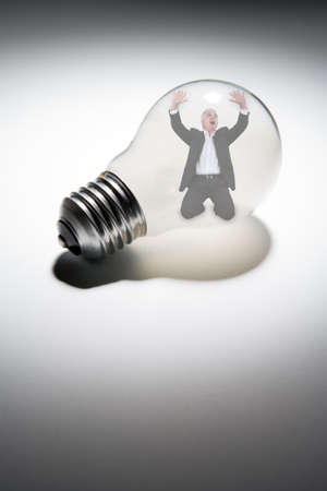 Senior businessman trapped in light-bulb photo