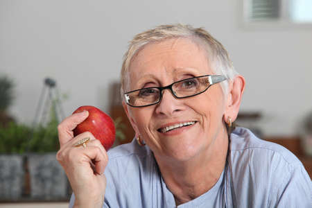 Senior woman with apple in hand photo