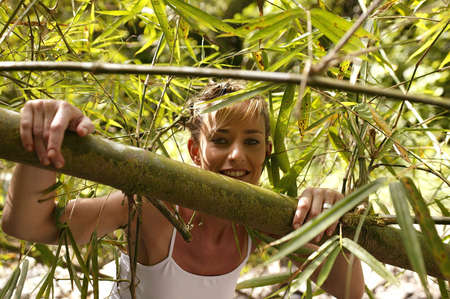 amongst: Attractive blond stood amongst branches Stock Photo