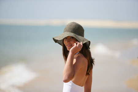 An attractive woman wearing a floppy hat at the beach photo