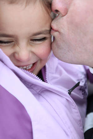 Father kissing daughter photo