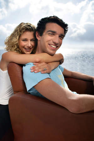 man and woman embracing on armchair photo