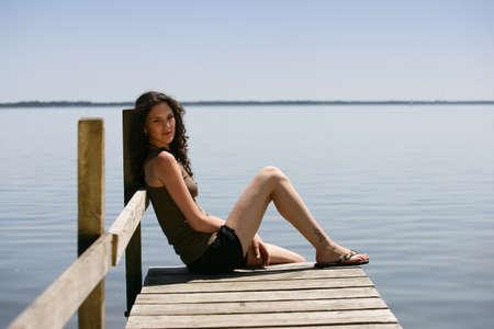 Woman sat on jetty Stock Photo - 12250887
