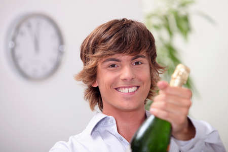corked: Young man with a bottle of champagne and a clock showing five to twelve Stock Photo