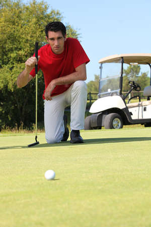 Golfer kneeling. photo