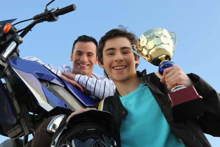 father and son holding trophy after motorbike race photo