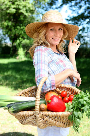 Pretty woman with a straw hat and basket of vegetables. photo